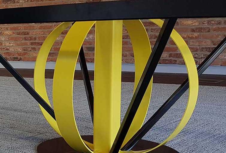 Metal yellow table leg designed like a globe